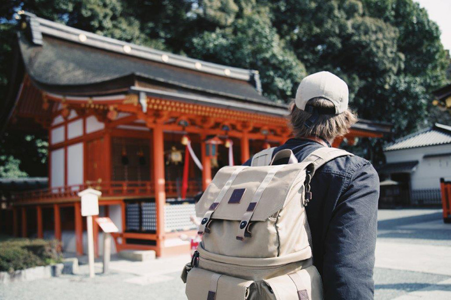 traveler in japan passing by a shrine